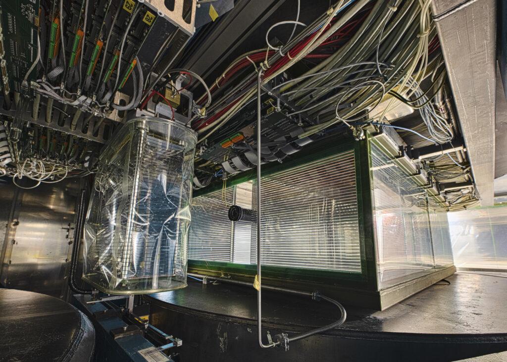 Wielkie, trójwymiarowe komory projekcji czasowej eksperymentu NA61/SHINE w CERN rekonstruują tory i identyfikują cząstki naładowane w wyprodukowane w zderzeniach ultrarelatywistycznych  jąder atomowych. Zderzenia te są rejestrowane w celu zbadania własności przejścia fazowego materii hadronowej w stan plazmy kwarkowo-gluonowej, znalezienia punktu krytycznego silnie oddziałującej materii, i określenia czasoprzestrzennej ewolucji tworzonego systemu za pomocą efektów elektromagnetycznych.